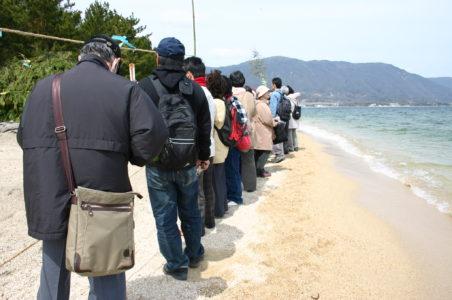 波打ち際で待つ人々